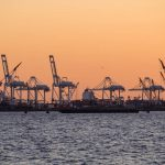 Free stock photo Industrial cranes at harbor against orange sky