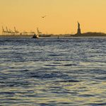 Free stock photo Distant sunset view of statue of liberty and river