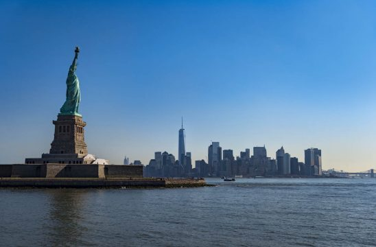 Free stock photo Statue of liberty with cityscape in background against blue sky