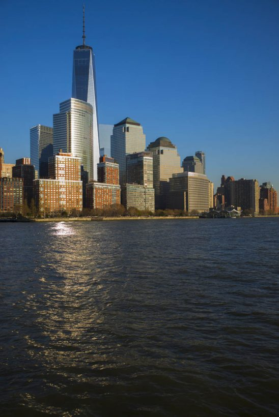 Free stock photo Skyscrapers and lower Manhattan by hudson river against blue sky