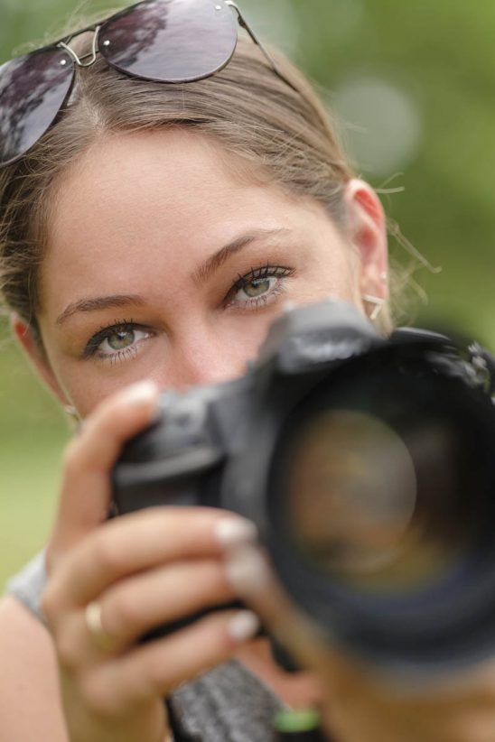 Free stock photo Close-up portrait of woman using dslr camera outdoors