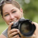 Free stock photo Close-up portrait of smiling woman using dslr camera outdoors