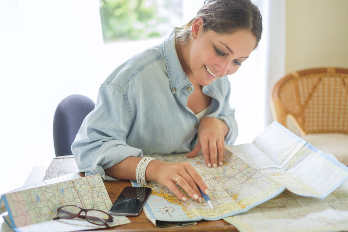 Free stock photo Smiling woman reading map while sitting at table