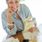 Free stock photo Portrait of smiling woman holding map at table