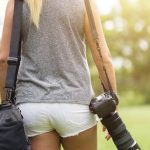 Free stock photo view of woman walking outdoors with camera and bag