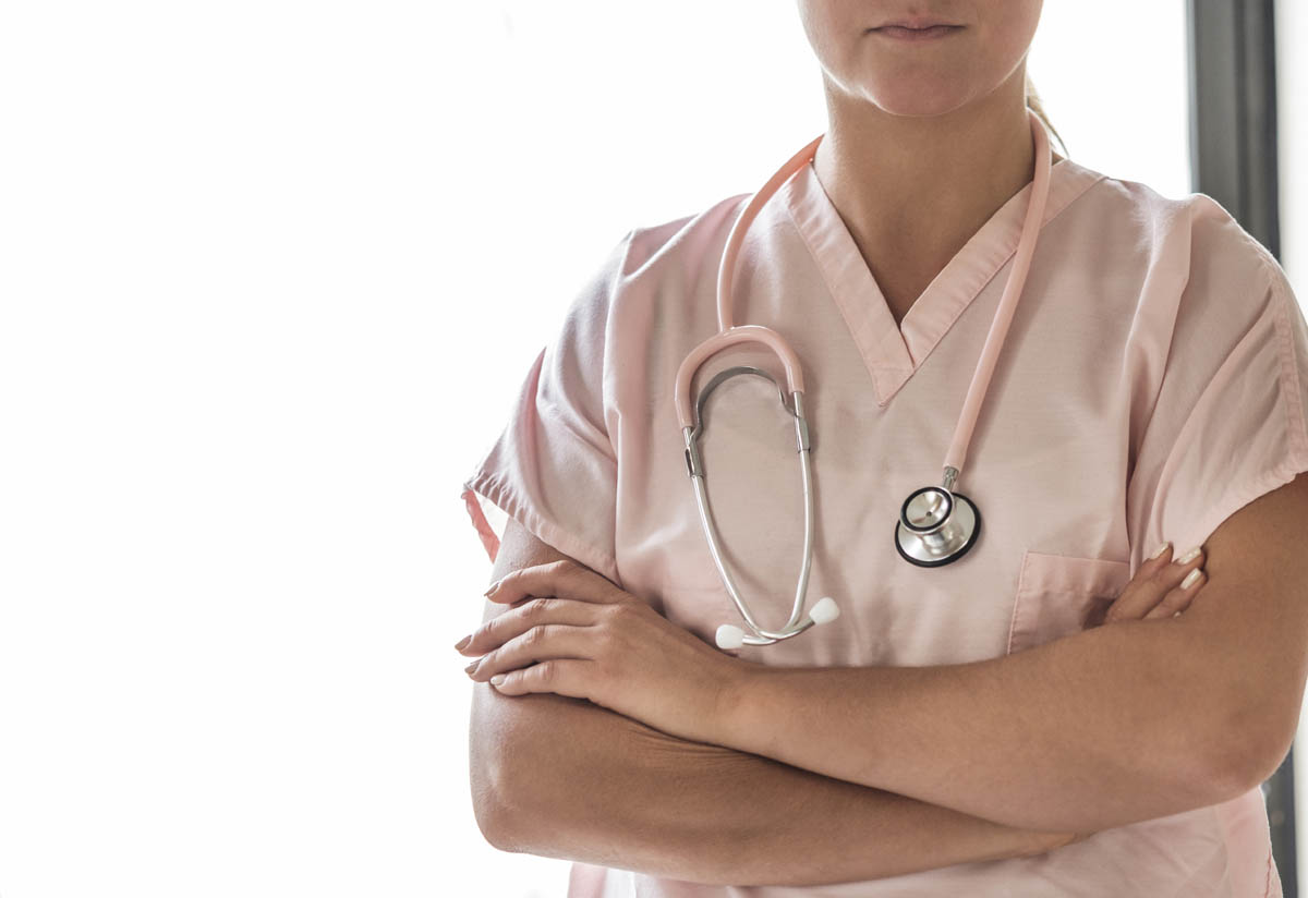 Free stock photo Partial view of female doctor standing arms crossed with stethoscope around neck