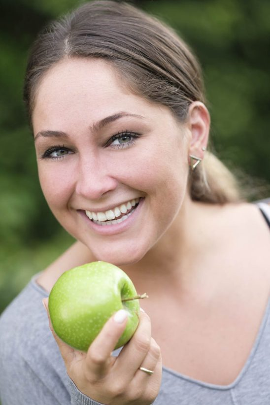 Free stock photo Portrait of smiling woman holding green apple