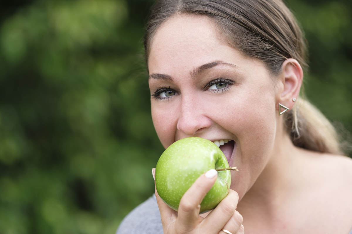 Free stock photo Portrait of woman eating green apple