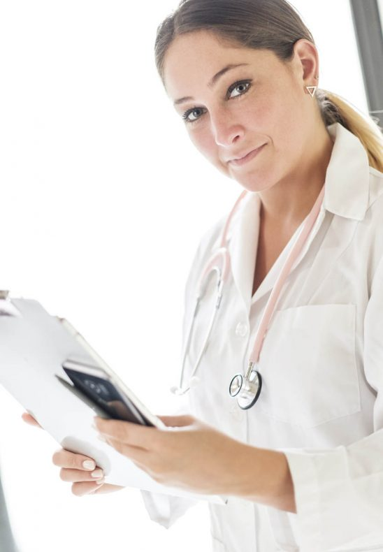 Free stock photo Portrait of female doctor holding mobile phone and clipboard in hospital