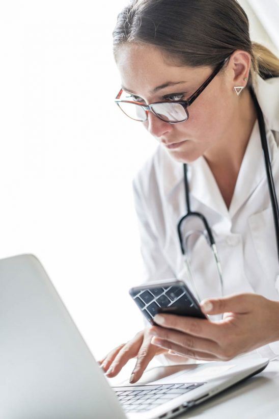 Free stock photo Female doctor holding mobile phone while using laptop over white background
