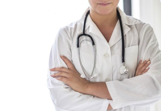 Free stock photo Midsection of female doctor standing arms crossed with stethoscope around neck at hospital