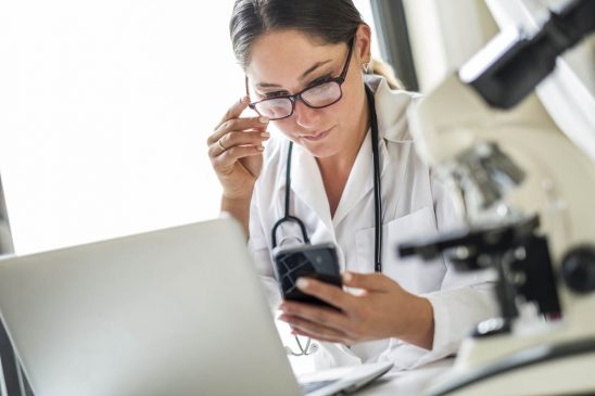 Free stock photo Female doctor adjusting eyeglasses while using mobile phone in laboratory