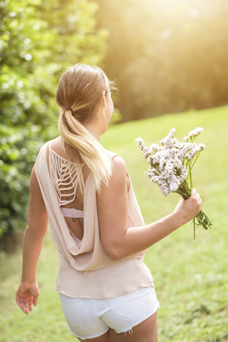 Free stock photo Rear view of woman holding flowers in park