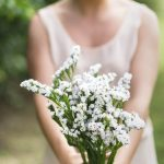 Free stock photo Smiling woman holding white flowers in park