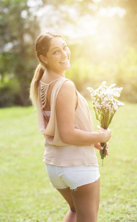 Free stock photo Portrait of smiling woman holding flowers in park