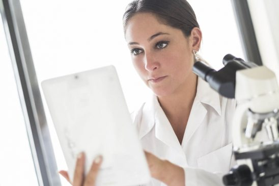 Free stock photo Confident female lab technician using digital tablet in laboratory