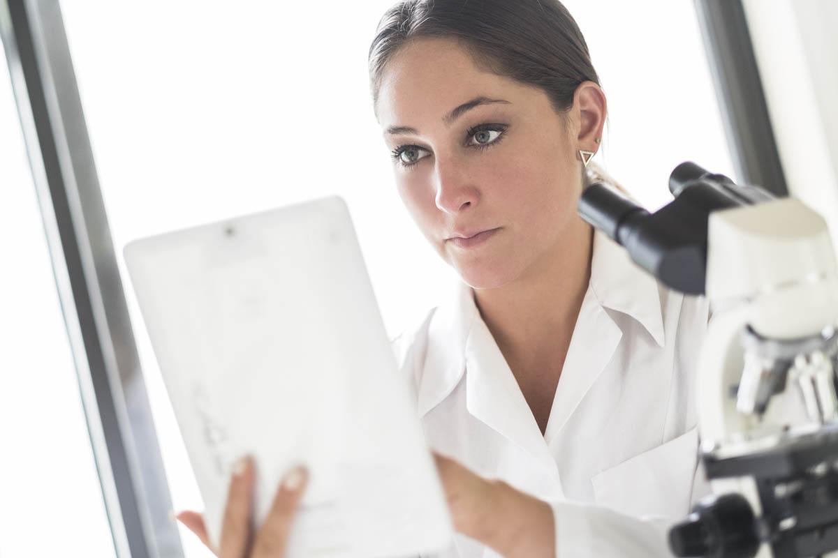 Free stock photo Confident female lab technician using digital tablet in laboratory