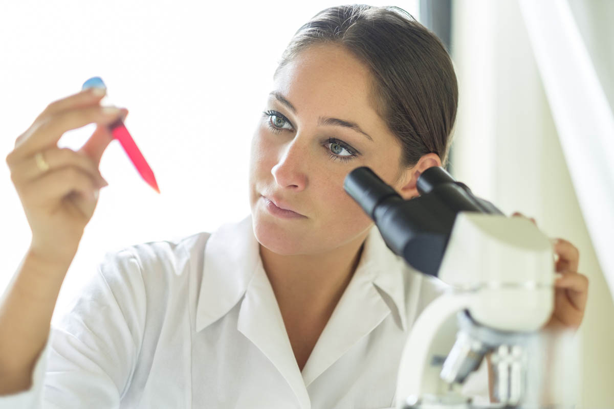 Free stock photo Confident female lab technician looking at solution in test tube in laboratory