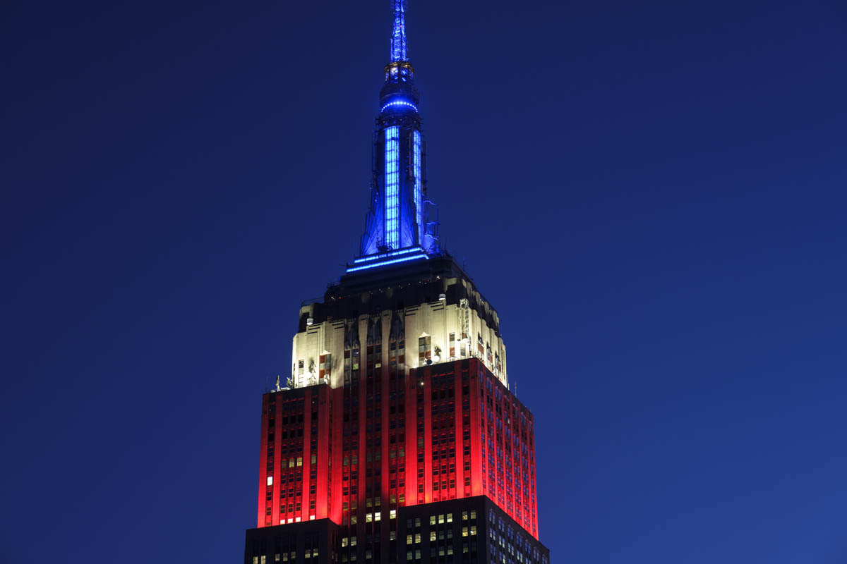 Free stock photo Lit view of red, white, and blue empire state building against blue sky