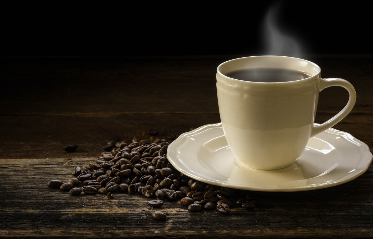 Free stock photo Hot coffee in cup by beans on wooden table