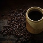 Free stock photo High angle view of coffee cup and beans on wooden table