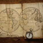 Free stock photo Close-up of vintage eyeglasses and compass on world map