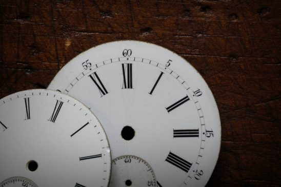 Free stock photo Close-up of pocket watch faces on wooden table
