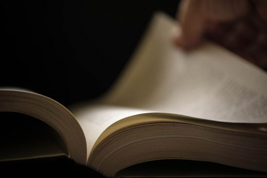 Free stock photo Close-up of hand turning a book page against black background