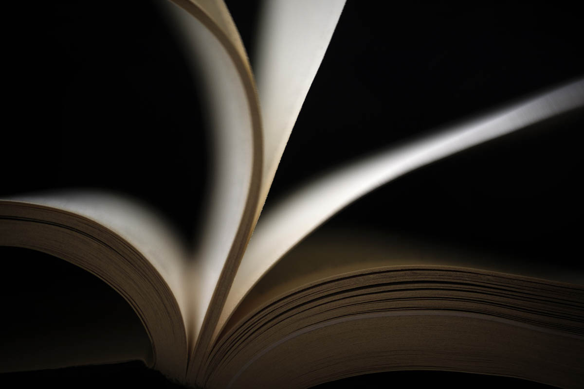 Free stock photo Close-up of book with pages turning against black background