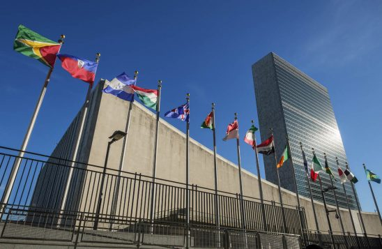 Free stock photo Low angle view of united nations and national flags against blue sky