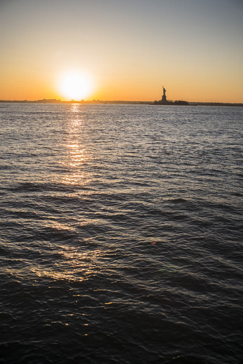 Free stock photo Distant view of statue of liberty with hudson river in foreground during sunset