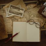 Free stock photo Antique world map with travel journal, photographs, and vintage camera