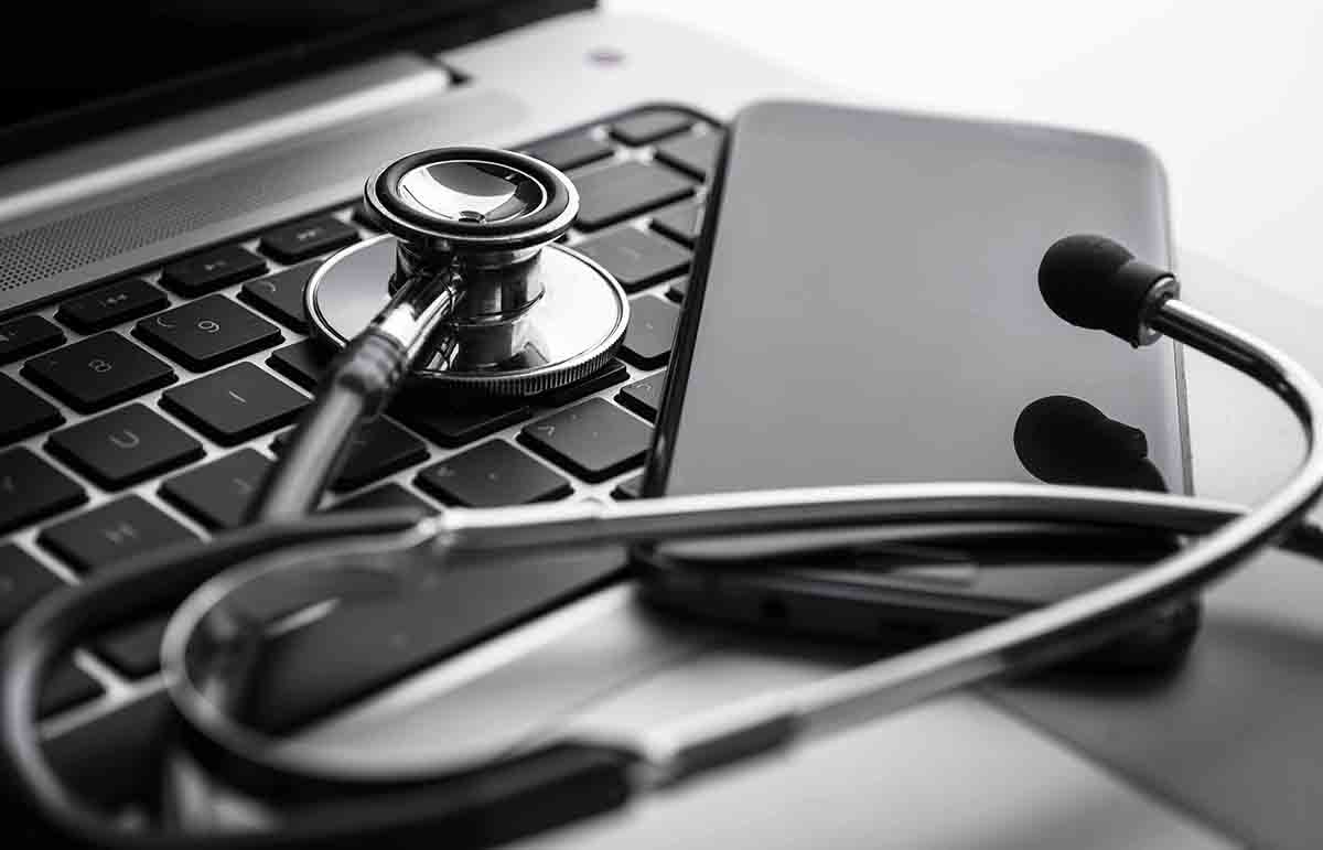 Free stock photo Close-up of stethoscope and smart phone on laptop keyboard