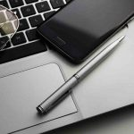 Free stock photo Close-up of pen by smart phone and eyeglasses on laptop keyboard