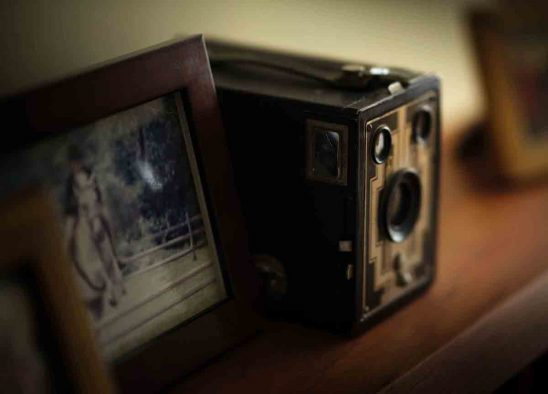 Free stock photo Close-up of vintage camera by picture frame on table