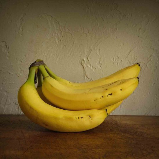 Free stock photo Close-up of bananas on wooden table against wall