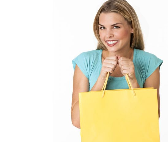 Free stock photo A young woman holding a shopping bag and smiling at the camera