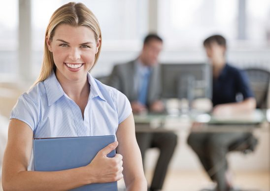 Free stock photo A young business woman smiling into the camera in her office