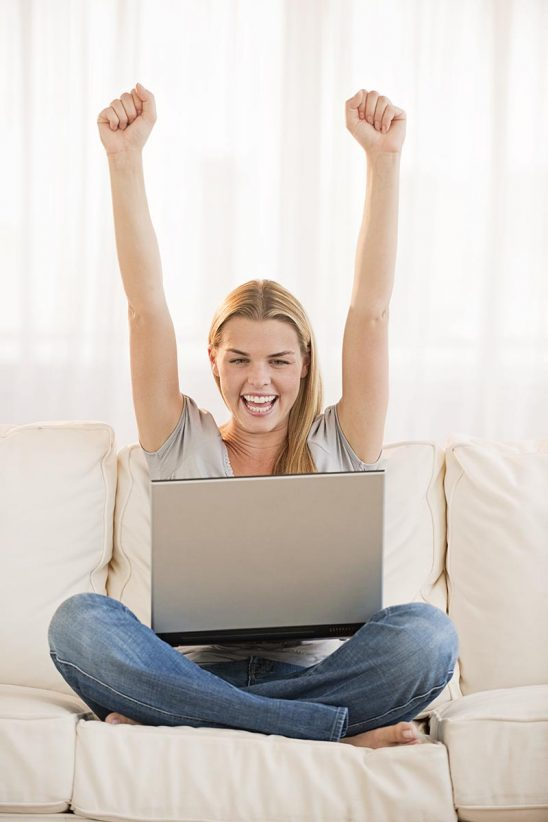 Free stock photo A smiling and excited young blonde raising her fists in the air