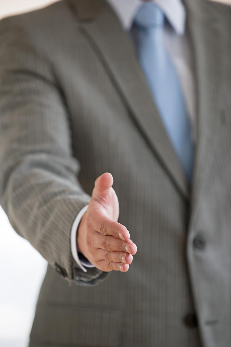 Free stock photo A businessman is extending his hand for a handshake