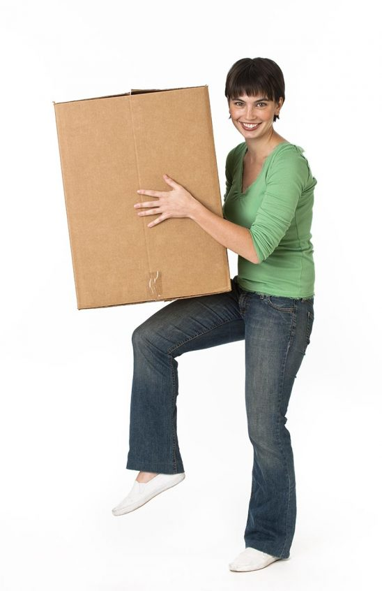Free stock photo A woman is holding a moving box and smiling at the camera