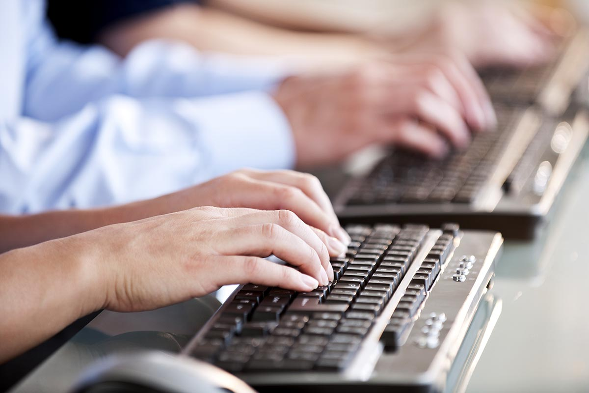 Free stock photo Close-up of several people's hands typing on computer keyboards.