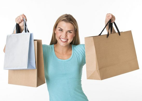 Free stock photo A young woman is standing and holding up shopping bags.