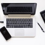 Free stock photo Laptop on a desk with cell phone and camera