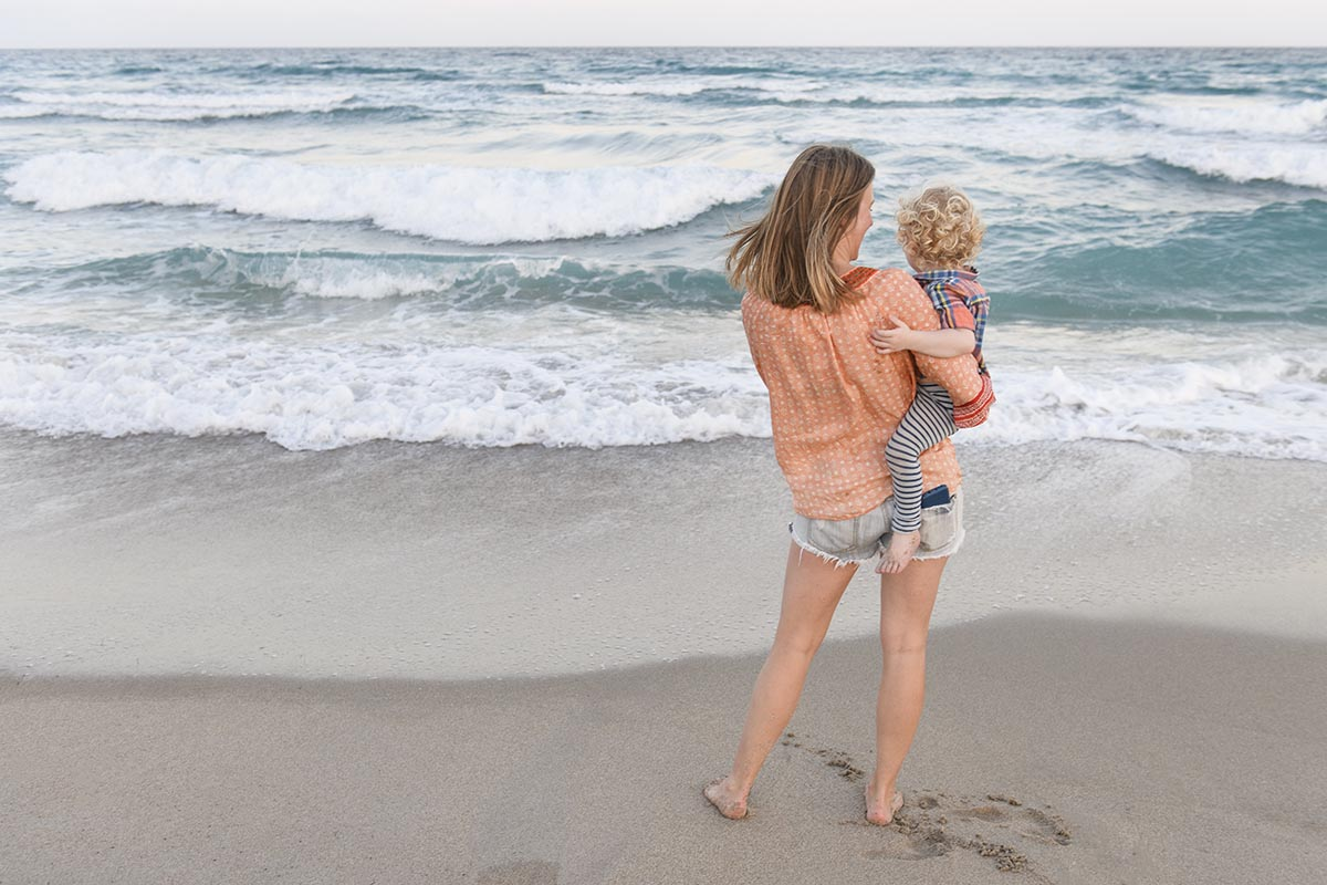 Free stock photo A mother with her child on a beach watching the ocean