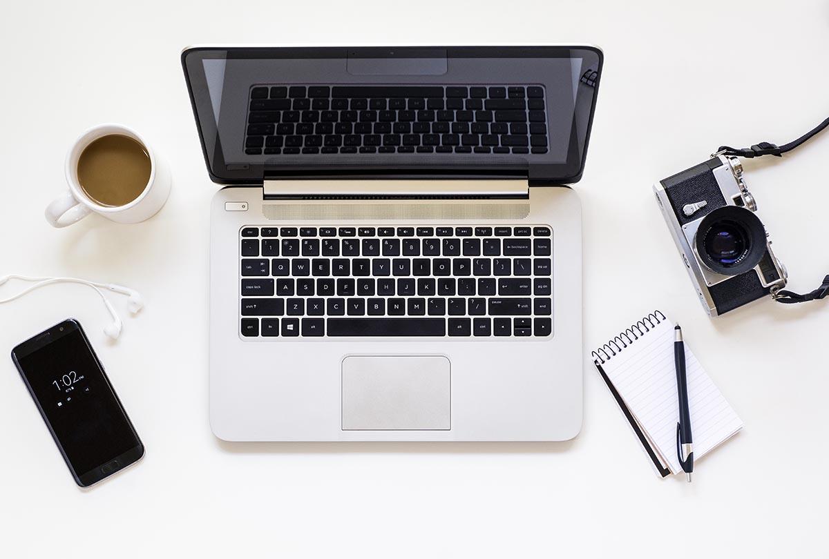 Free stock photo Laptop on a white desk with cell phone and retro camera