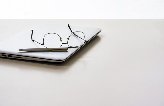 Free stock photo Closed laptop on a white desk with glasses