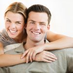 Free stock photo Portrait of a young couple posing together and smiling at the camera
