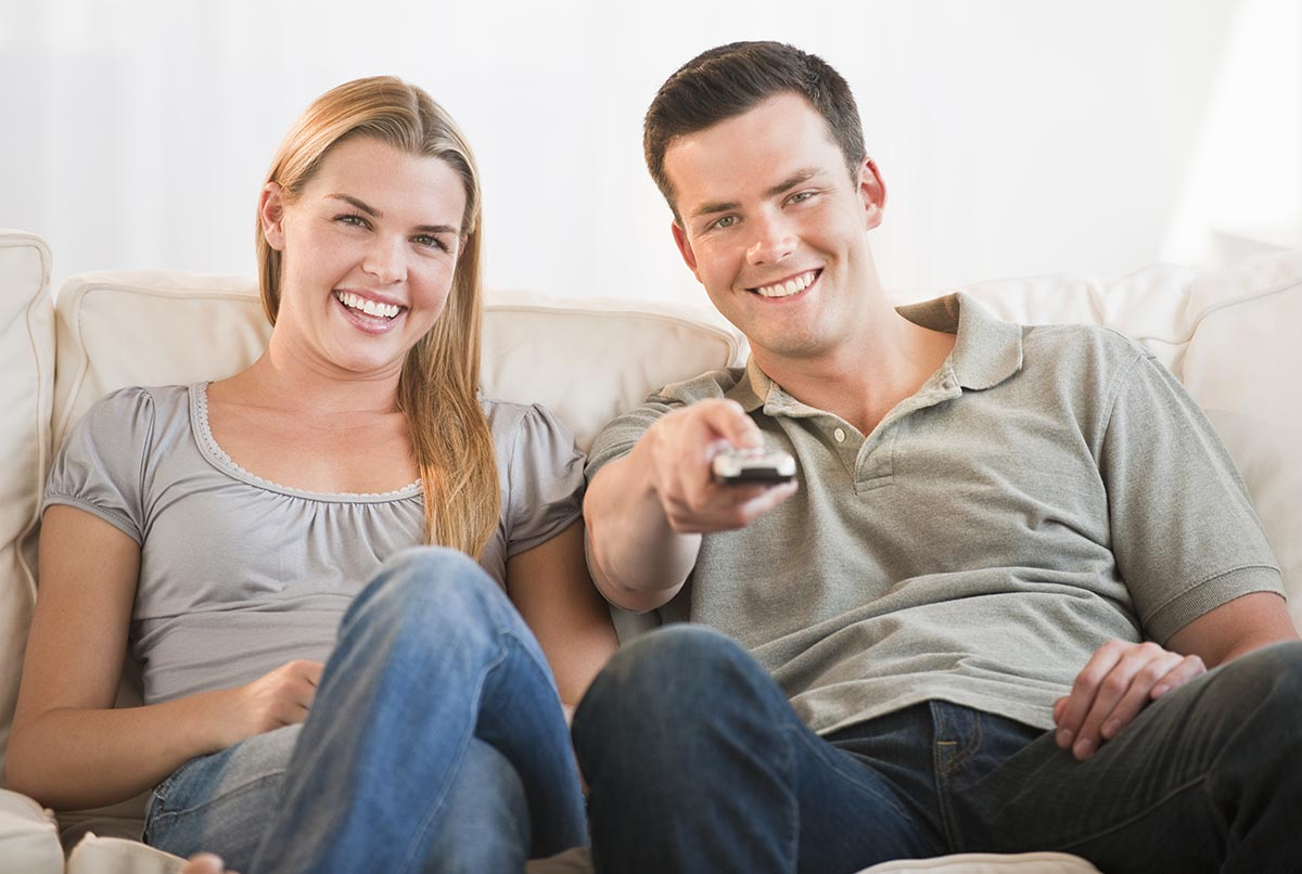 Free stock photo Young couple watching TV together, smiling with the man holding a remote control