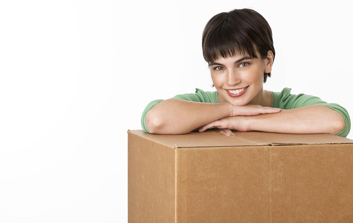 Free stock photo A young brunette resting her arms on a cardboard box